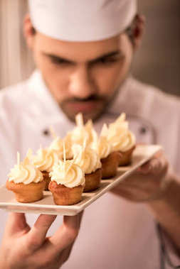 selective focus of confectioner looking at cupcakes on plate in hands