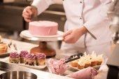Oříznout záběr cukrář takže dort v kuchyni restaurace