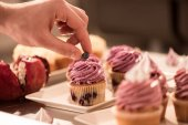 Photo cropped shot of confectioner decorating sweet cupcake with berry