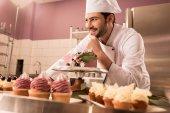 Fotografie usmívající se cukrář stojí u pultu s dort a koláčky v kuchyni restaurace