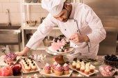 Fotografie portrét cukrář zdobení dortu v kuchyni restaurace