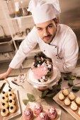 Fotografie vysoký úhel pohledu cukrář stojící poblíž dort na pult v kuchyni restaurace