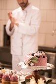 Fotografie Selektivní fokus dort, cupcakes a cukrář v kuchyni restaurace