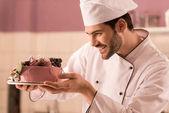 Fotografie boční pohled na usmívající se cukrář pohledu na dort v ruce v kuchyni restaurace