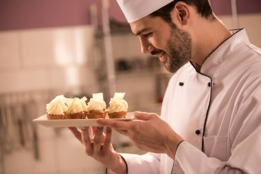 side view of smiling confectioner looking at cupcakes on plate in hands