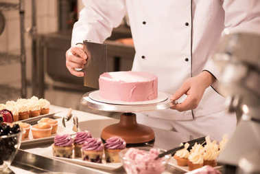 cropped shot of confectioner making cake in restaurant kitchen