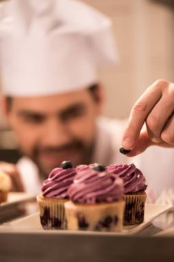 selective focus of confectioner decorating cupcakes with berries in restaurant kitchen