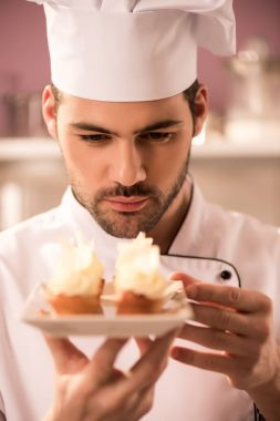 portrait of focused confectioner looking at cupcakes on plate in hands