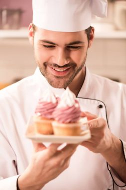 portrait of smiling confectioner looking at cupcakes on plate in hands