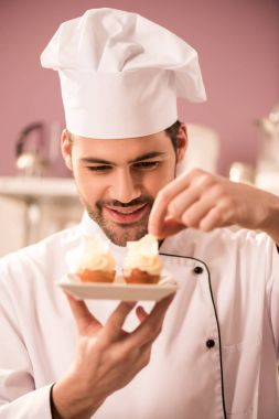 portrait of smiling confectioner decorating cupcakes in restaurant kitchen