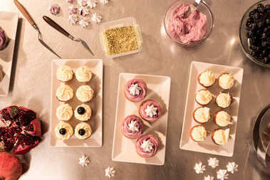 top view of arranged sweet cupcakes on plates on counter in restaurant kitchen