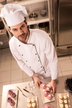 high angle view of confectioner in chef hat standing at counter with desserts in restaurant kitchen