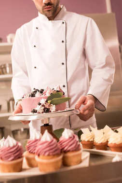 partial view of confectioner holding cake in restaurant kitchen
