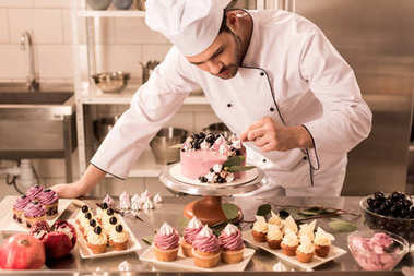 portrait of confectioner decorating cake in restaurant kitchen
