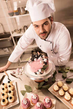 high angle view of confectioner standing near cake on counter in restaurant kitchen