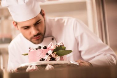 selective focus of confectioner looking at cake in hands in restaurant kitchen
