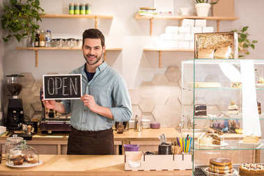 Smiling barista with open blackboard in hands at counter in coffee shop stock vector