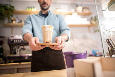 Selective focus of barista with ice coffee in hands in cafe stock vector
