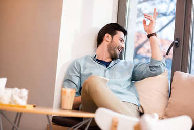 cheerful man looking out window in coffee shop