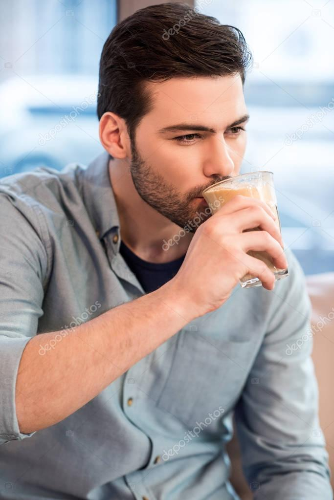 portrait of young handsome man drinking ice coffee in cafe