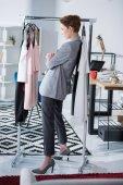 Fotografie ernsthafte Modedesigner stehen unter Rack mit Kleidung