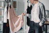 oříznutý snímek mladé módní návrháře zkoumá kvalitu oblečení na ramínkách