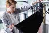 vážnou módní návrhář zkoumá kvalitu oblečení na ramínkách