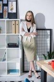 Fotografia Stilista attraente che si appoggia su scaffali ufficio