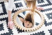 giovane donna attraente che guarda lobbiettivo attraverso riflessione a specchio