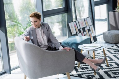 attractive young fashion designer using smartphone in armchair at office