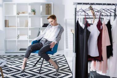 stylish fashion designer sitting in chair at modern office