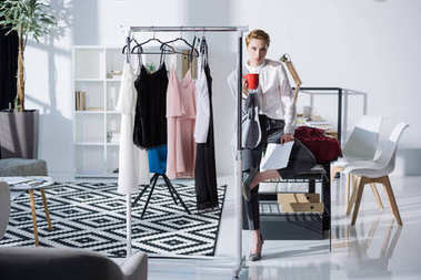 young stylish fashion designer sitting on desk at office