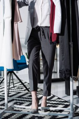 cropped shot of stylish woman standing between clothes hanging on rack
