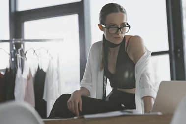 stylish fashion designer sitting on work desk at office