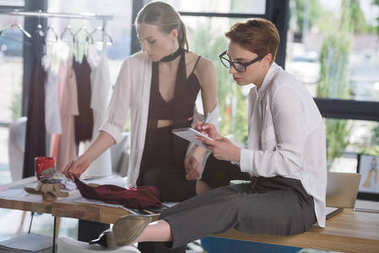 stylish young fashion designers working together at clothing design studio
