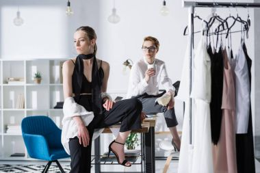 stylish young fashion designers sitting on work desk at office