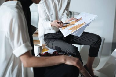 croped shot of fashion designers sitting on table and discovering sketches