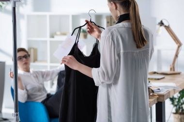 young fashion designers discussing new dress on hanger