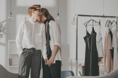 young fashion designers lesbian couple flirting at office
