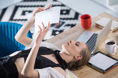 attractive fashion designer lying on desk and looking at sketch