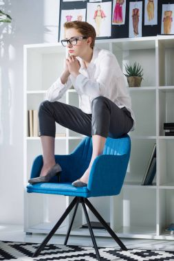 thoughtful stylish fashion designer sitting on chair at modern office