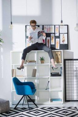 stylish fashion designer sitting on bookshelves and reading magazine