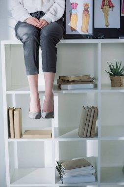 cropped shot of stylish woman sitting on bookshelves