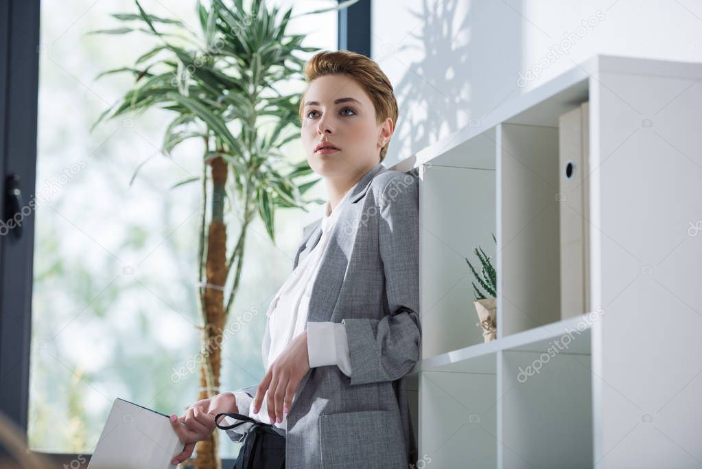 attractive young businesswoman with book leaning back on bookshelves at office