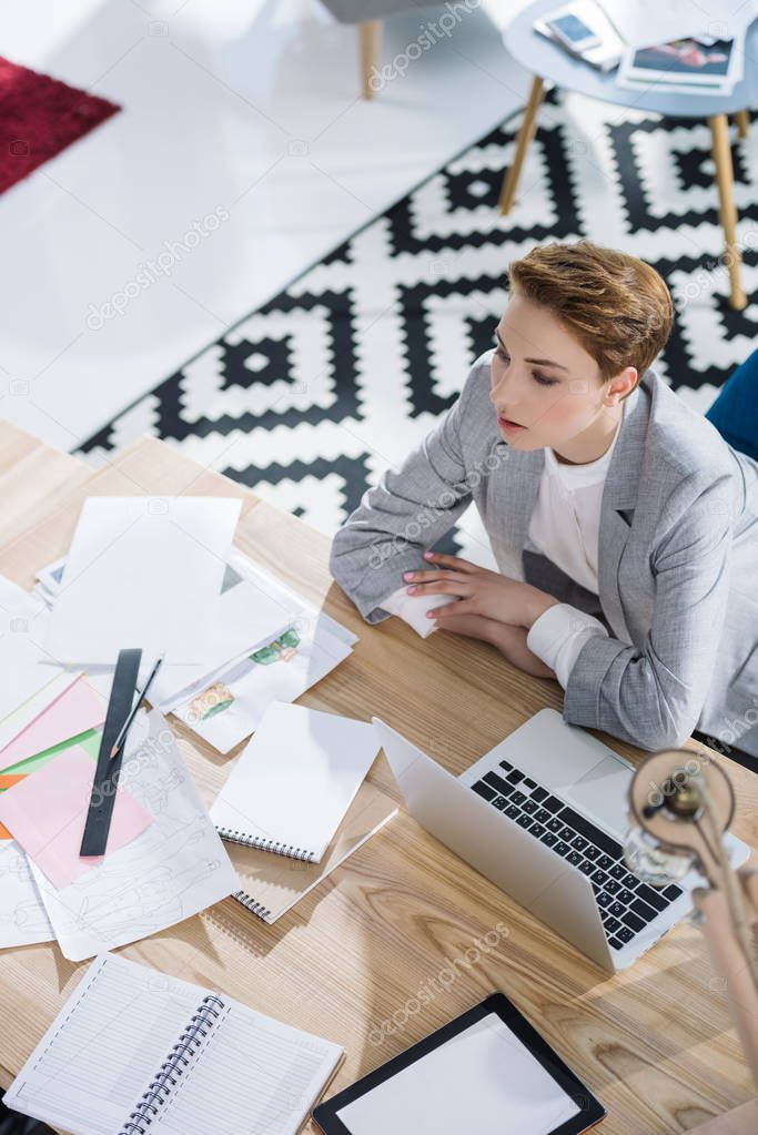 high angle view of stylish young businesswoman sitting at workplace in office