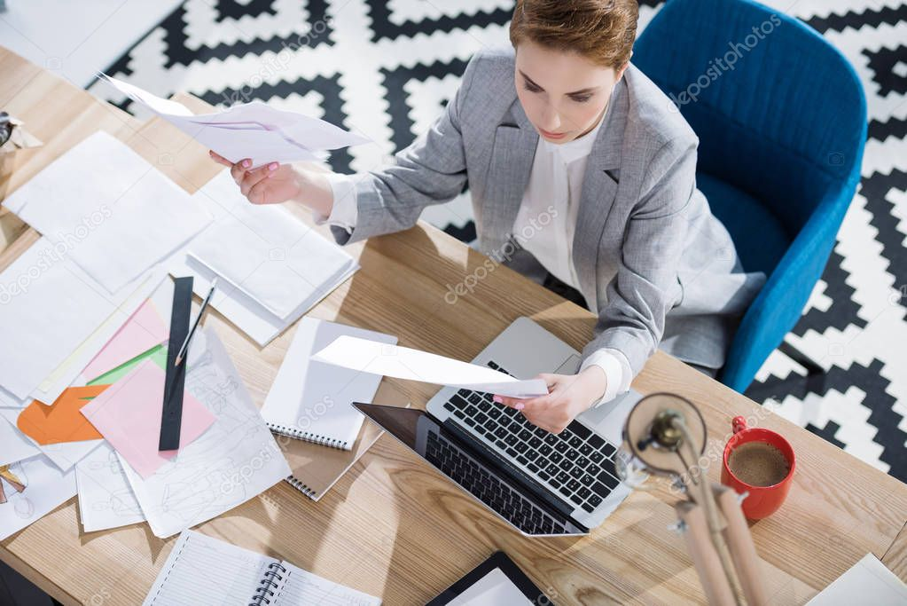 high angle view of stylish young businesswoman doing paperwork at office