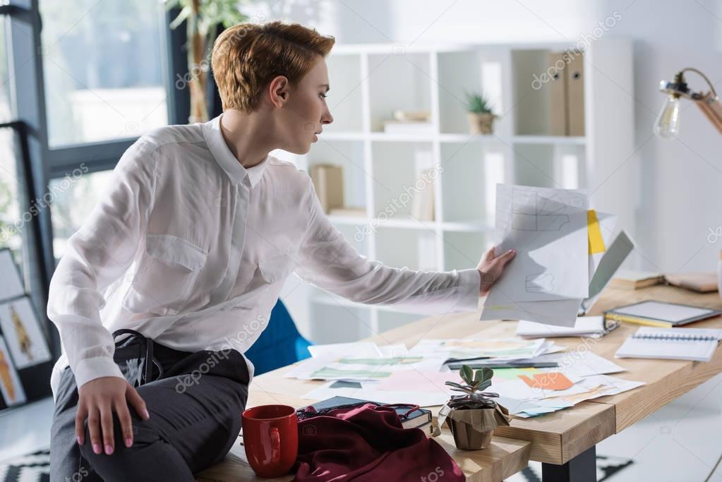 stylish fashion designer with lot of paperwork sittin on work desk