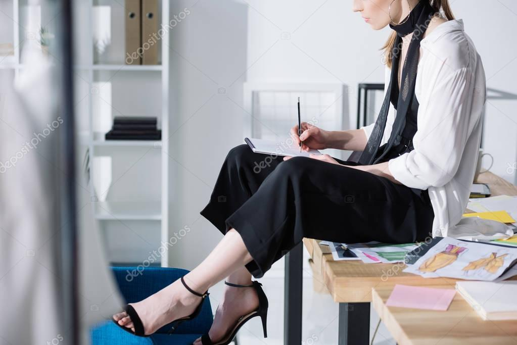 cropped shot of fashion designer drawing in album while sitting on work desk