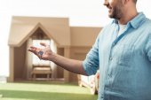 šťastný muž, který držel klíč nové lepenkové domu izolované na bílém