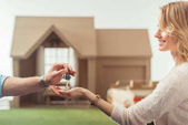 Photo cropped shot of real estate agent passing key to happy woman in front of cardboard house
